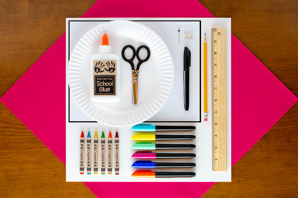 materials for Surreal Creature Craft including colorful crayons and markers, scissors, white school glue, paper plate, ruler, brad, pin and pencil
