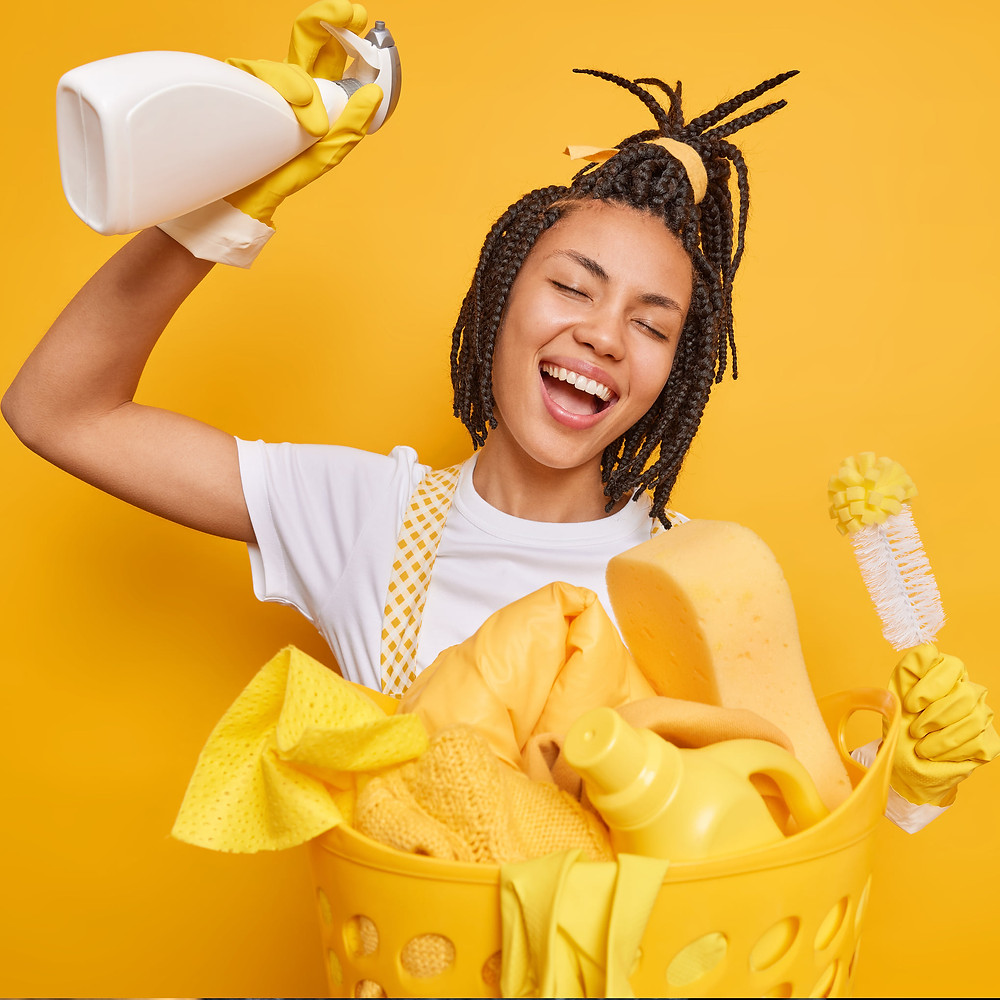 Joyous woman being creative while cleaning on yellow background