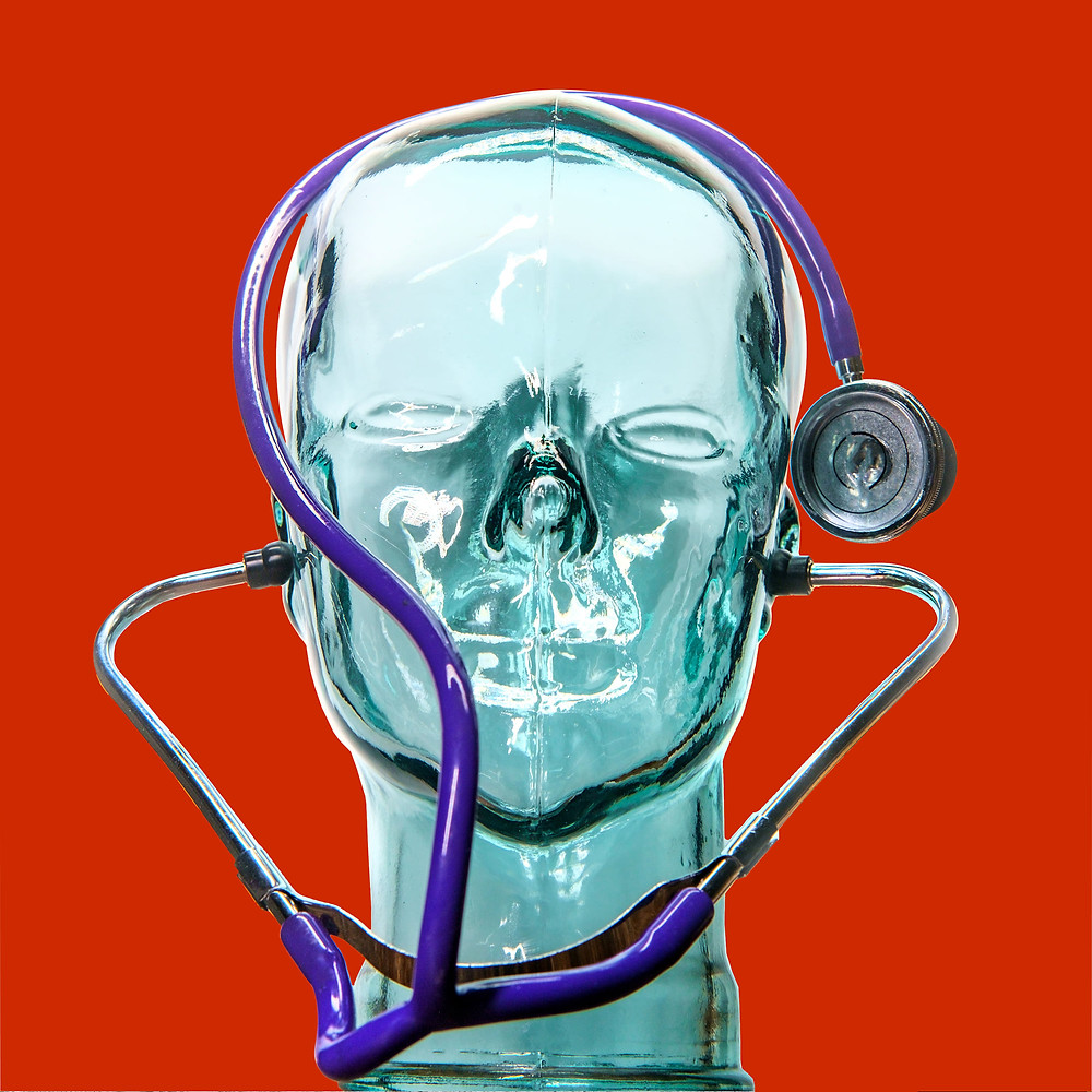 glass head sculpture on red wearing stethoscope on red background as a reminder that creativity is important for a healthy mind, body, and soul