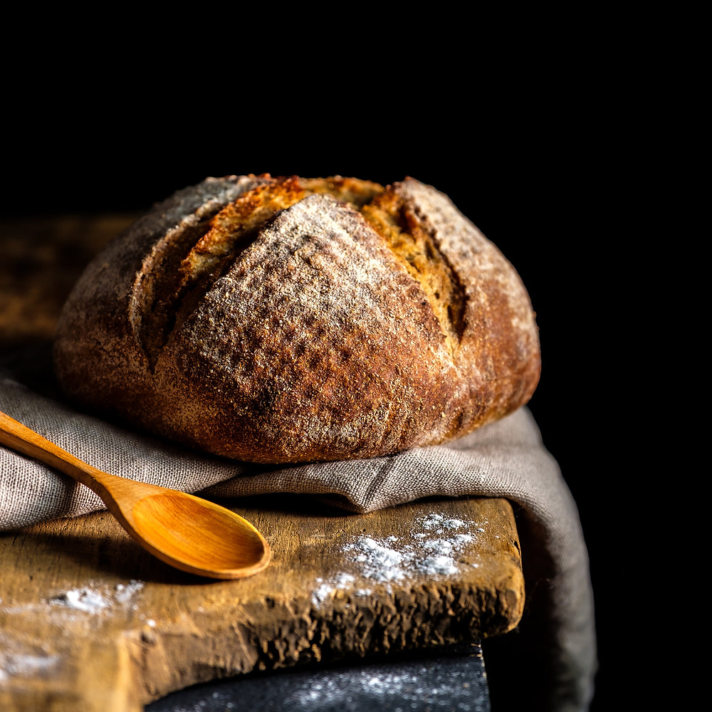 Sourdough bread loaf with wooden spoon on wooden countertop with black background