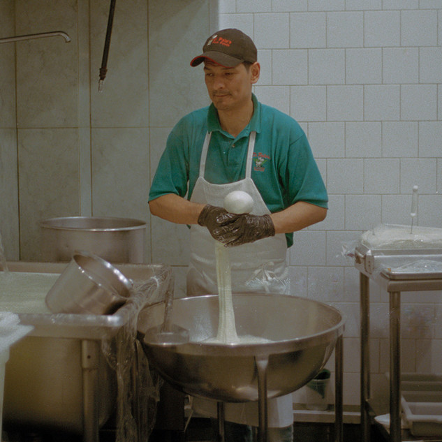 Rene Alvarado, age 41 prepares fresh mozzarella cheese at Di Palo's. Rene Is originally from Colombia, and has been working at the Di Palo's store for over 10 years. Feb. 16, 2016. Little Italy, New York