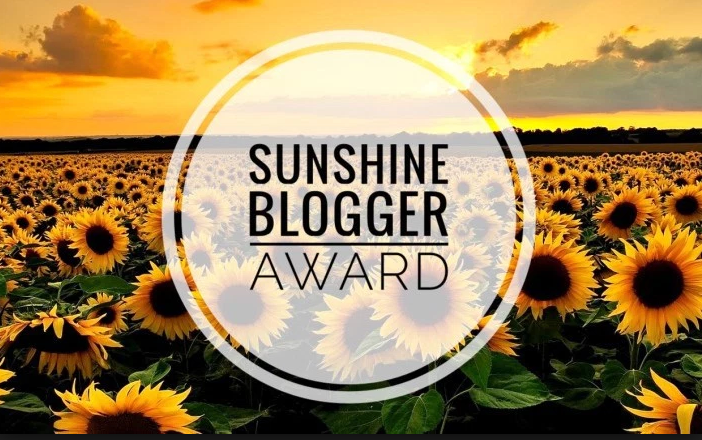 Sunshine Blogger Award text on a field of Sun Flowers Given to Disabled Disney