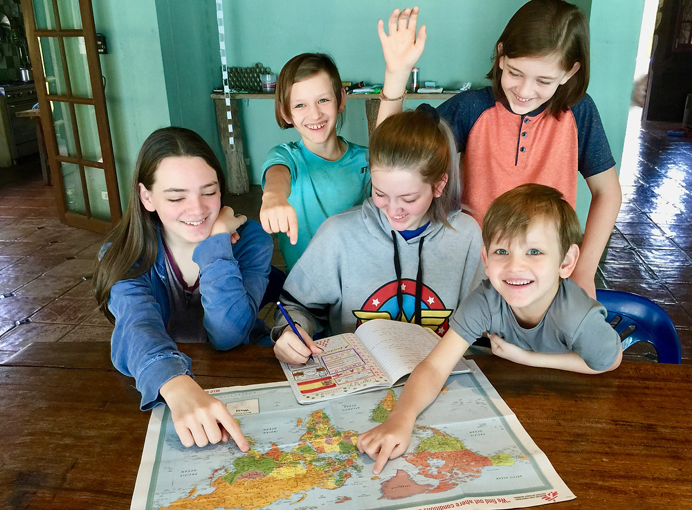 Children looking at a map planning a vacation.
