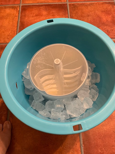 Blue bucket filled with ice holding container