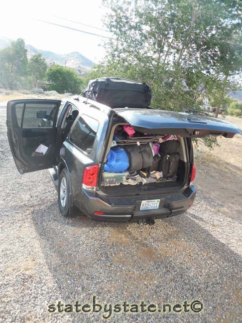 A car with luggage, sleeping bags and personal items packed in the trunk.