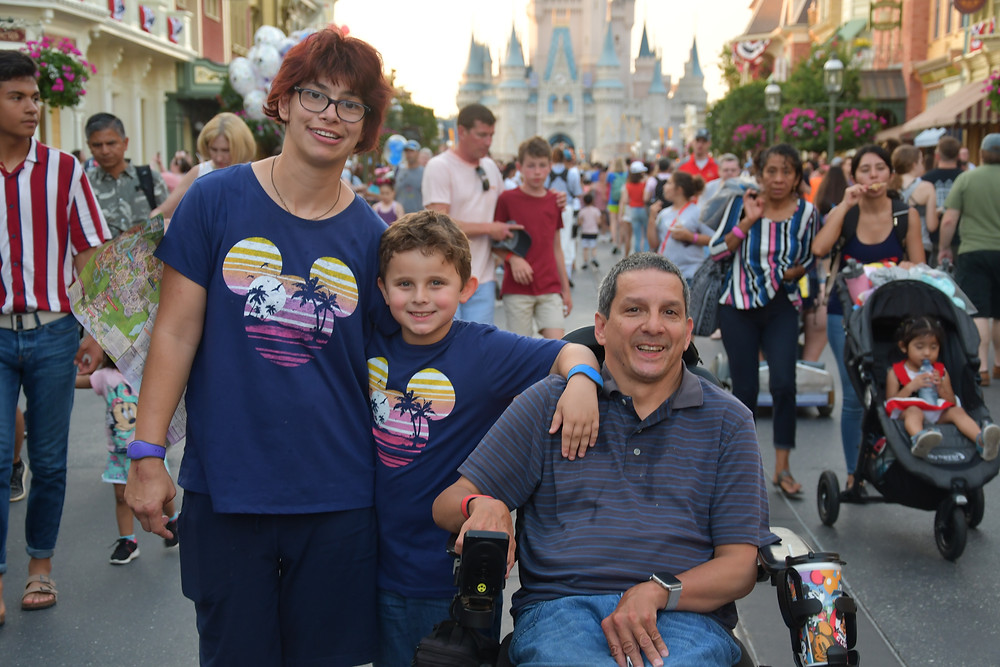 man in power wheelchair, with son and wife both wearing dark blue shirts with Mickey silhouette. With Cinderella's Castle in background.