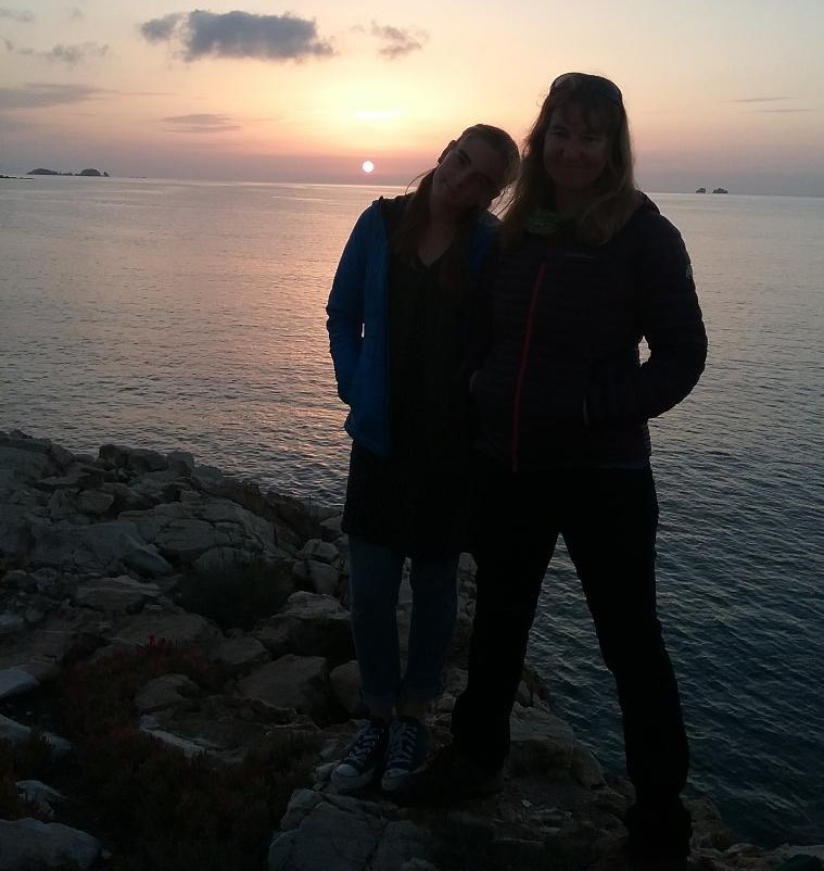 2 people on a cliff, ocean in background at sunset