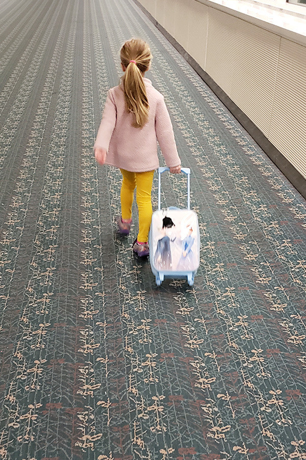 Little girl walking with a suitcase