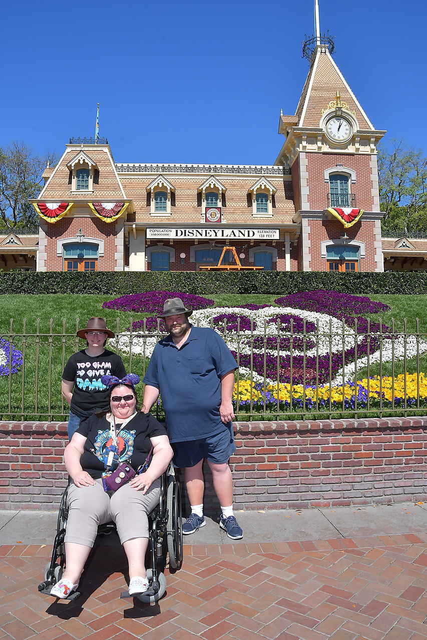 Melissa, David and Gillian from Disabled Disney posing in front of the Mickey topiary in Disneyland