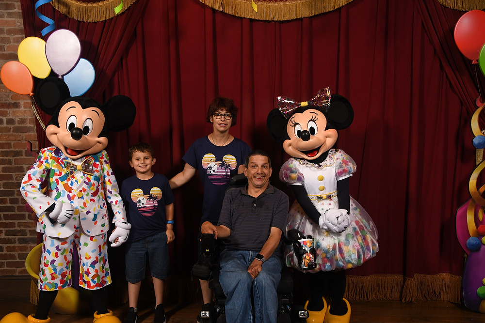 a man in a power wheelchair wearing a dark grey shirt and jeans, a woman wearing a blue shirt with a Mickey silhouette standing behind him and a boy wearing a dark blue shirt with a Mickey silhouette standing next to the woman. Minnie and Mickey Mouse are on the ends.