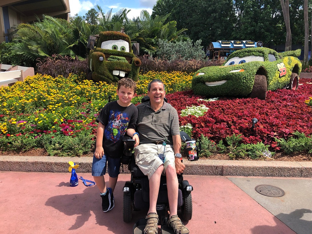 a flower display with Tow Mater and Lightning McQueen from Cars in the background. Glenn from Wheelchair Daddy sitting in his power wheelchair wearing a grey shirt and khaki shorts. His son wearing a black shirt and jean shorts standing next to him.n