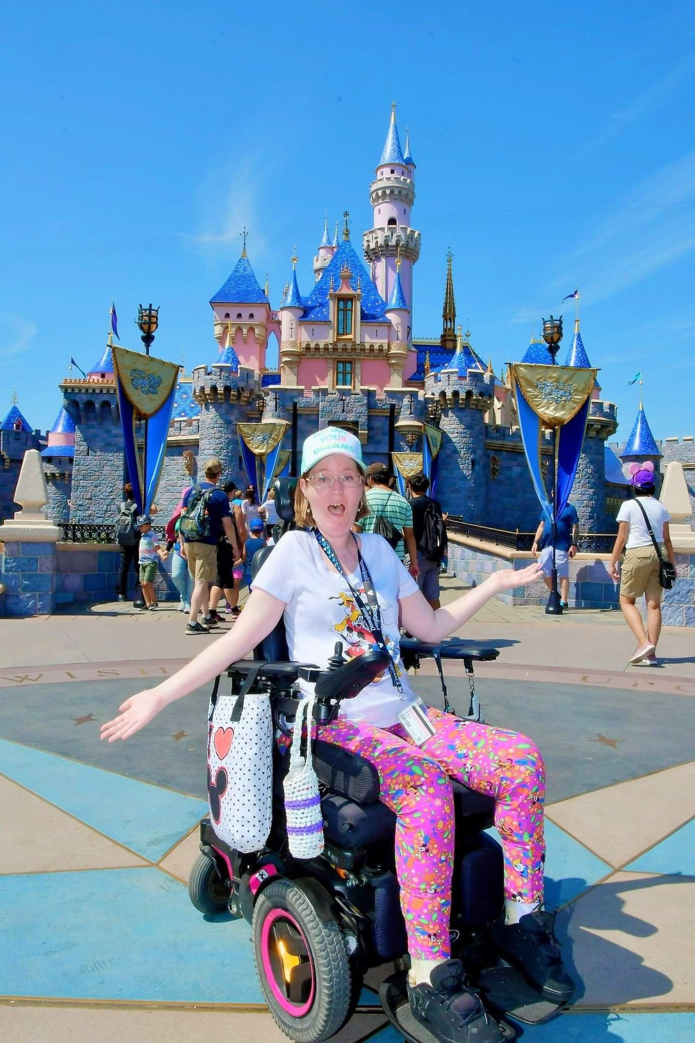 Angela in a power wheelchair posing in front of Sleeping Beauty Castle at Disneyland