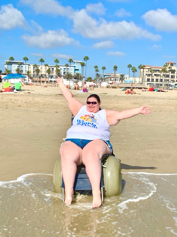 a woman wearing a tank top and jean shorts in a beach wheelchair on the beach