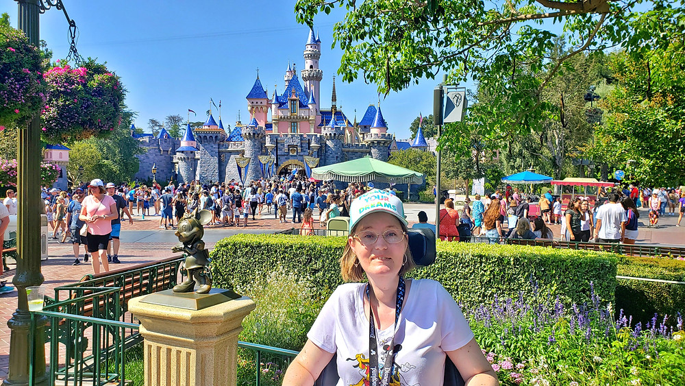 woman in a power wheelchair wearing a hat that says follow your dreams with the Disneyland Castle behind her