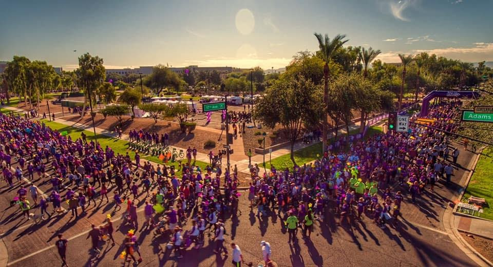 a group of people over 20,000 wearing purple and walking to end Alzheimer's