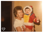an older woman holding a young child wearing a rainbow colored snow suit