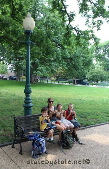people sitting on a park bench having a picnic