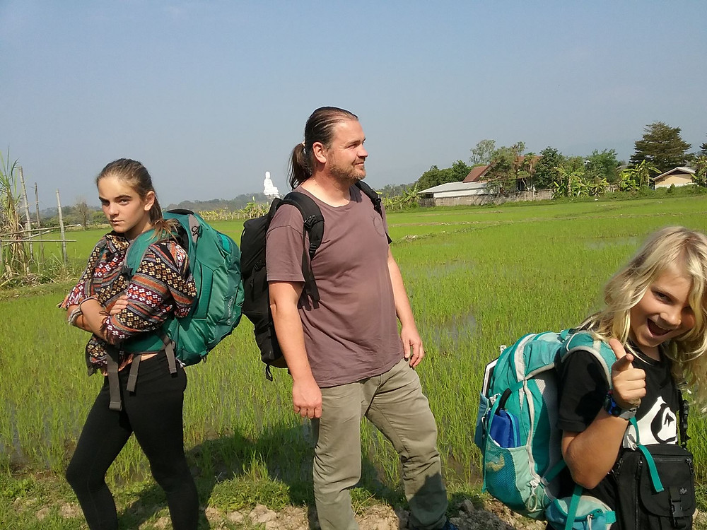 2 children female, 1 adult male standing in a rice fiield