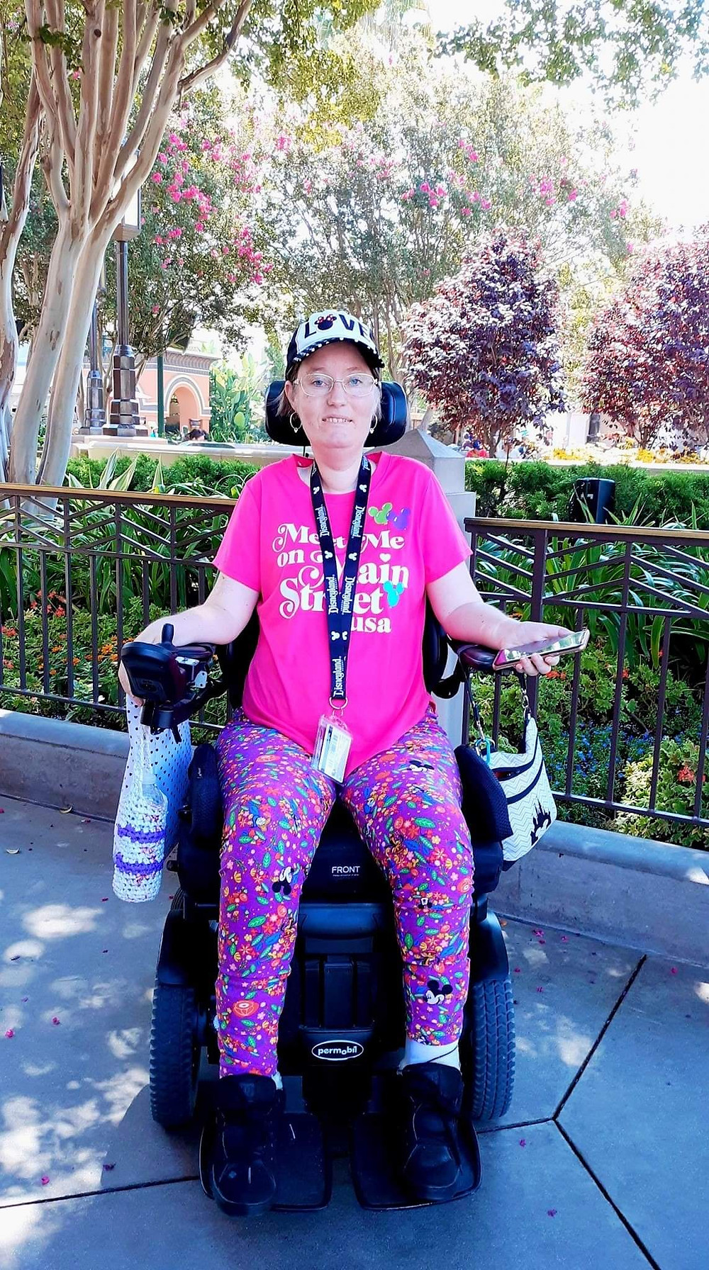 woman in a power wheelchair wearing a pink shirt. Disneyland trees and hedges behind her