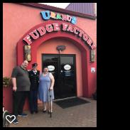 3 people standing in front of a door and sign for Uranus Fudge Factory in MO