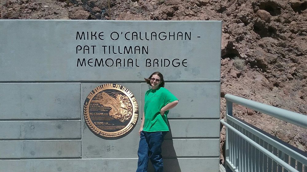 My daughter standing at a sign for the Mike O'Callaghan-Pat Tillman Memorial Bridge at Hoover Dam.