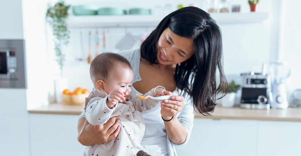 happy-young-mother-feeding-her-cute-baby