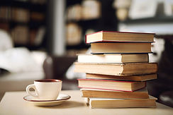pile of books on table with teacup and saucer