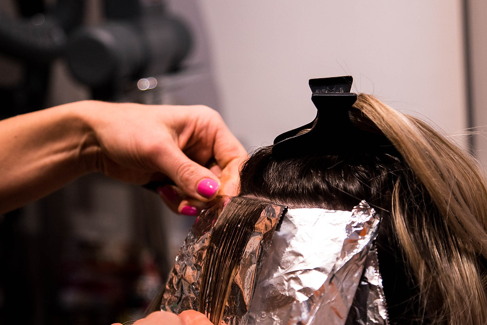 Hairstylist Emily Hafele placing foils to lighten her clients hair.