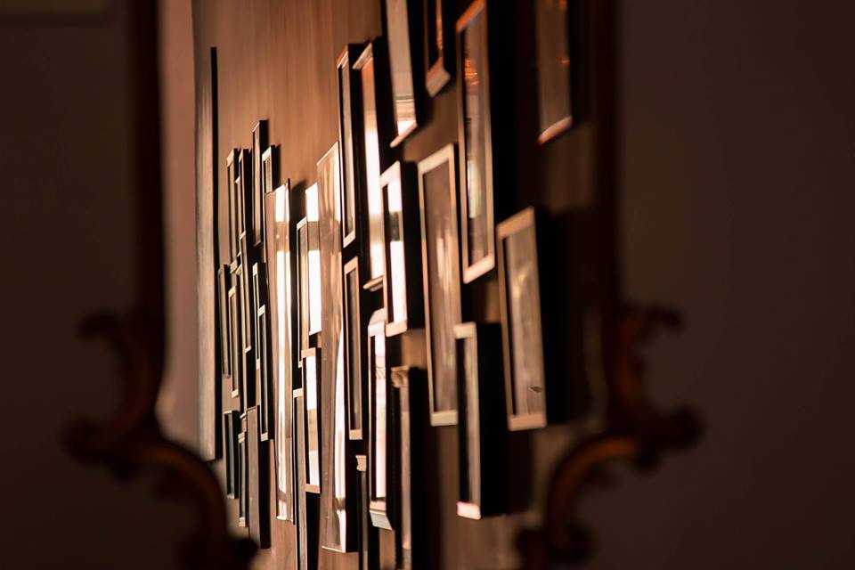 A reflection of the hallway frames on the wall into a cintage mirror at the end of the hall.