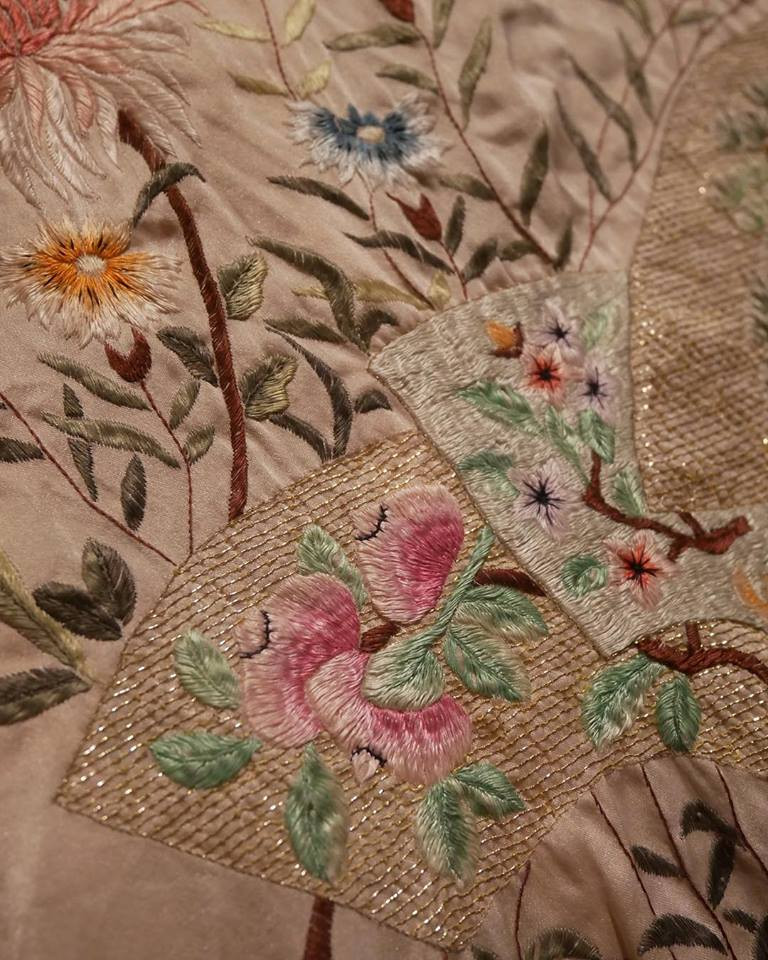 Close up of a vintage embroidered robe hanging in the massage studio.