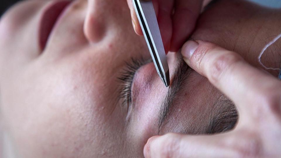 Close up shot of Kat Kass shaping eyebrows with tweezers