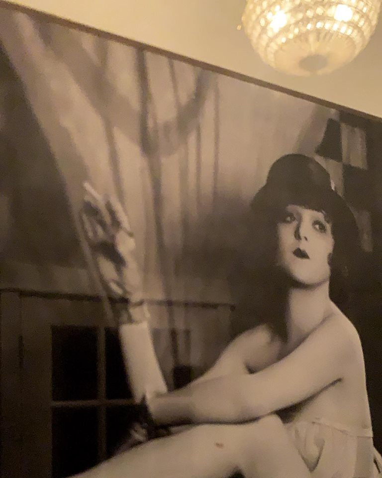 Photograph of a framed vintage photograph of a 20s actress posing confidently with a cigarette and the reflection of the hallway chandellier is visible in it.