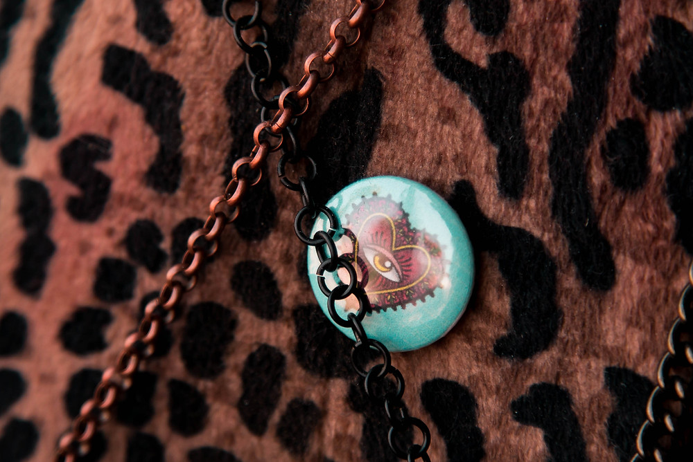 Close up of Mia X Marks the Spots logo pin displayed on her leopard print manequin in between the chains of her handmade crossbody bags,