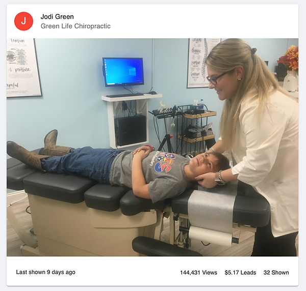 Dr. Jodi Green giving a young boy a chiropractic adjustment of the neck