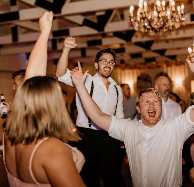 Wedding guests dancing the night away under a chandelier.