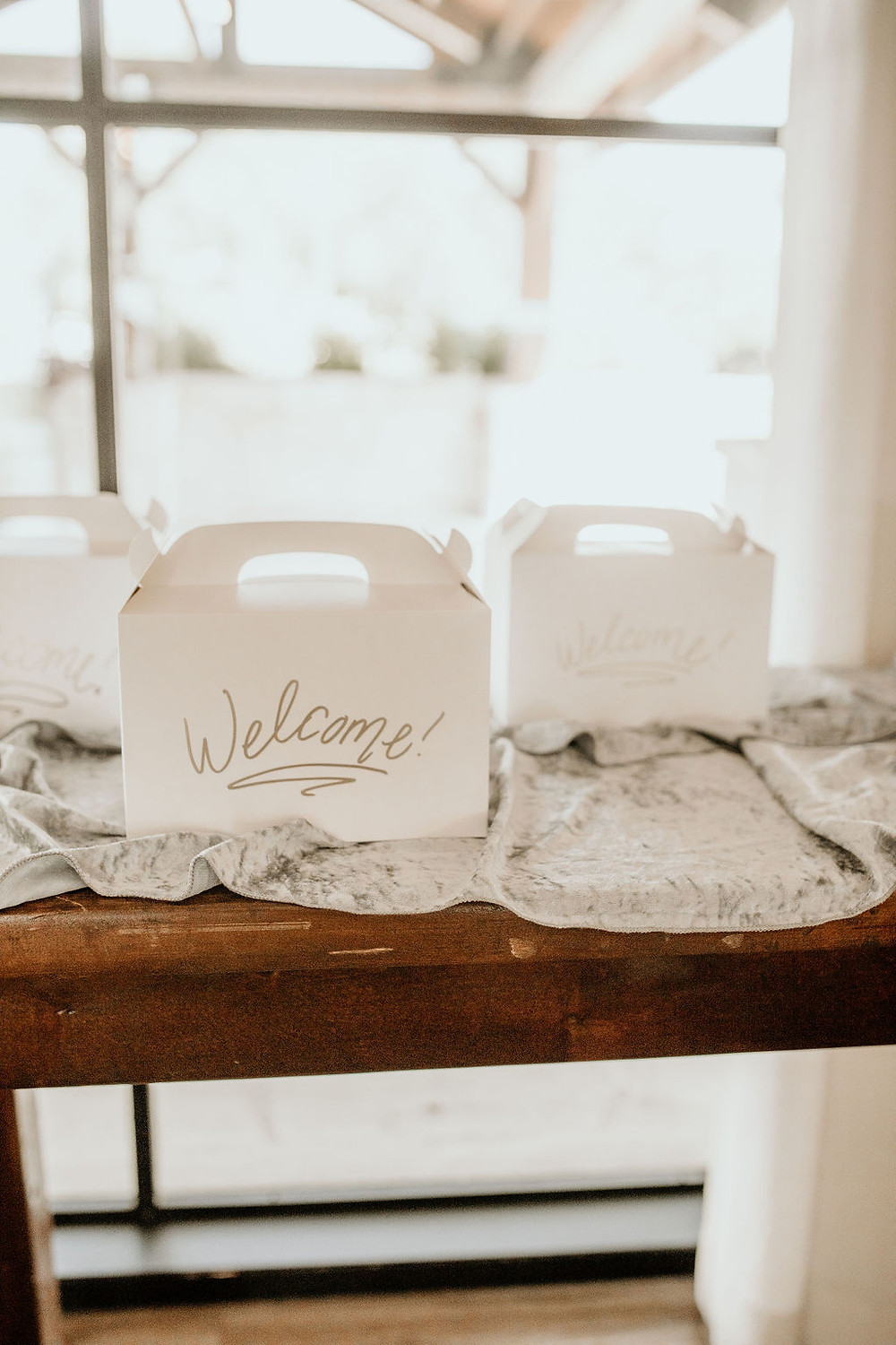 Wedding welcome bags on display in wedding venue on wooden farm table.
