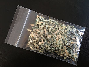 Photo of a glassine envelop full of shredded money