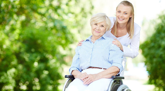 caregiver-pushing-senior-woman-wheelchai