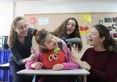 Three volunteers playing with a young girl