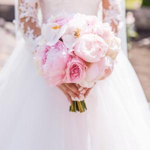 bride-rich-dress-holds-pink-wedding-bouquet-orchids-peonies.jpg