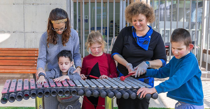 Three children and 2 therpaists playing the xylophone