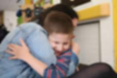 Young boy hugging his volunteer
