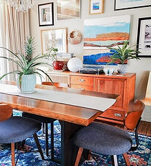 Scandi modern boho Dining Room with gallery wall, blue patterned area rug, vintage sideboard and live edge dining table