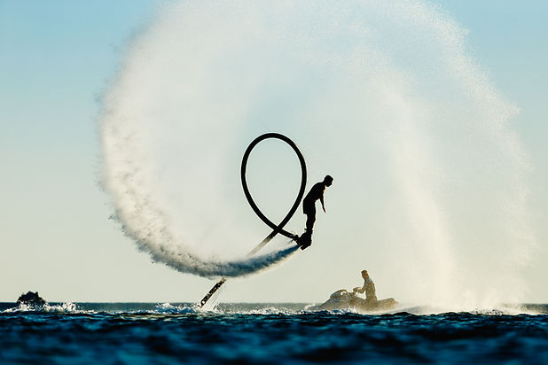 Silhouette of a fly board rider at sea.j