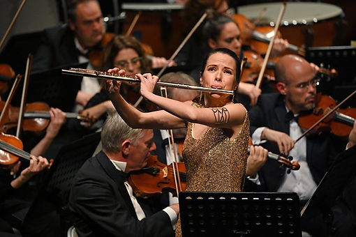 Woman in a gold dress playing her flute standing in front of an orchestra