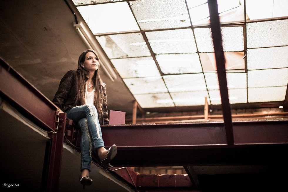 Woman in a brown leather jacket and ripped jeans sitting