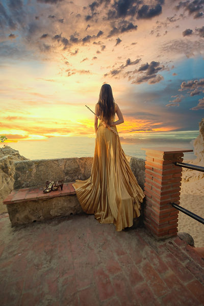 Woman in a gold dress holding a flute standing on a bench looking out to the sunset over the ocean