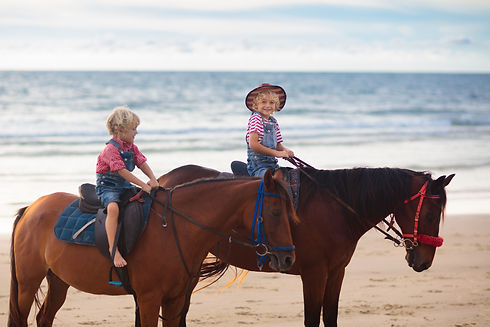 Kids riding horse on beach. Children rid