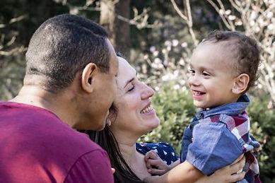 Foto de uma família num local com muitas árvores. A mãe segura a crianças no colo e olha para ela. A criança sorri e olha para o pai, que está ao lado.
