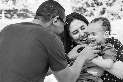 Foto em preto em branco de uma família. A mãe segura a criança no colo, e o pai faz coçegas nela.